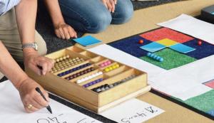 Viele bunte Montessori-Lernmaterialien sind auf dem Boden ausgebreitet. Jemand schreibt große Zahlen auf ein Blatt.
