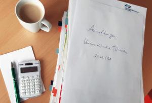 Großer Papierstapel mit Anemdlungen für das Schuljahr 2022/23, Kaffeetasse und Taschenrechner auf dem Schreibtisch.